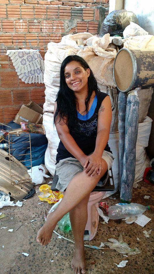 A catadora Cacilda Souza sentada em um banco improvisado para a gravação de seu vídeo: um vaso sanitário abandonado em um terreno baldio, cheio de larvas de mosquito, por ela reaproveitado